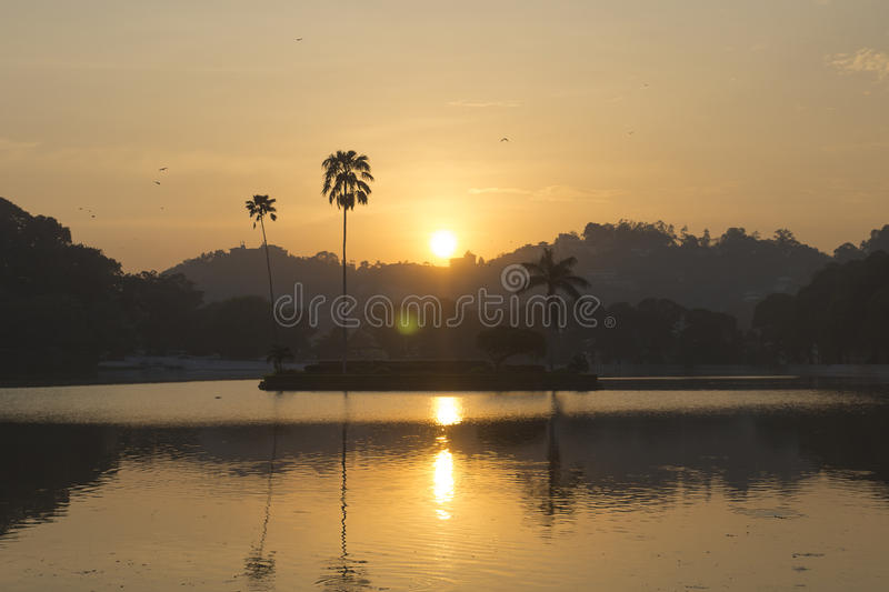 Sunset at Kandy Lake, Sri Lanka. Sun setting behind the mountains and a lake with an island and a palm tree royalty free stock images