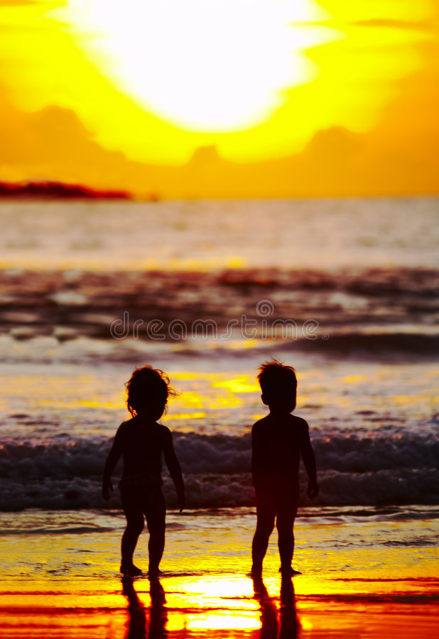 Sunset kids. View of two kid's silhouettes on the beach during sunset royalty free stock image