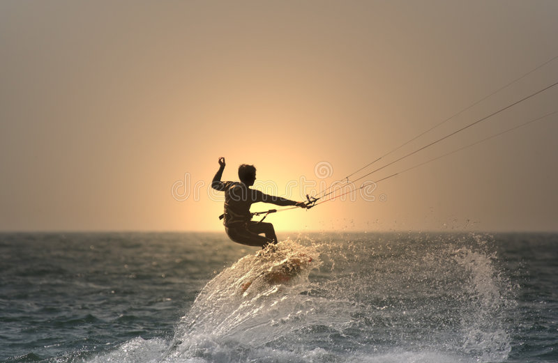 Sunset kitesurfer. Flying over a wave stock photography