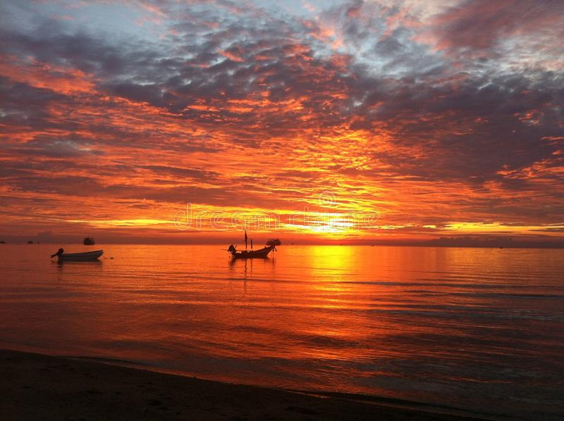 Sunset in Koh Tao. The most stunning sunsets can be seen off the beaches in Koh Tao. The thai long boats in the distance depict life in this beautiful country royalty free stock images