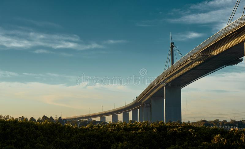 Melbournes Westgate Bridge against a dynamic blue sky and the vibrancy of colors from a low sun. Westgate bridge in Melbourne on a beautiful, slightly cloudy royalty free stock photo