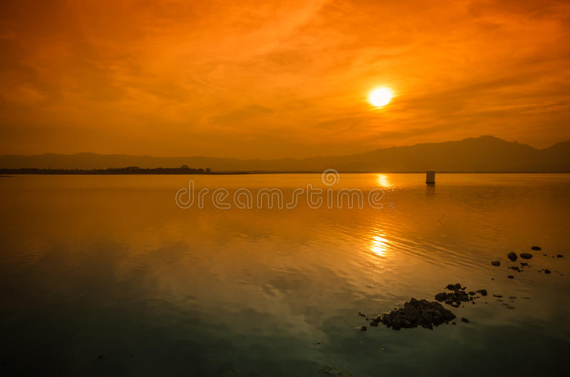 Sunset on the lake against the sky in the clouds. Beautiful sunset on the lake against the sky in the clouds royalty free stock photo