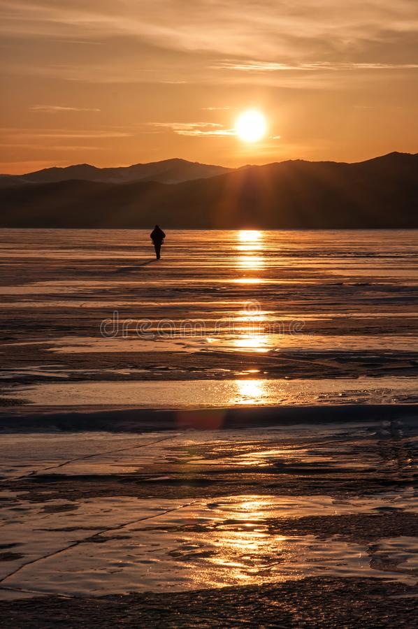 Sunset on the lake Baikal in winter with silhouette of man royalty free stock image