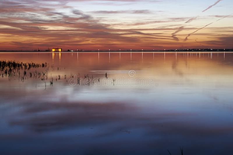 Sunset on the lake. Beautiful clouds reflected in the water. royalty free stock photography