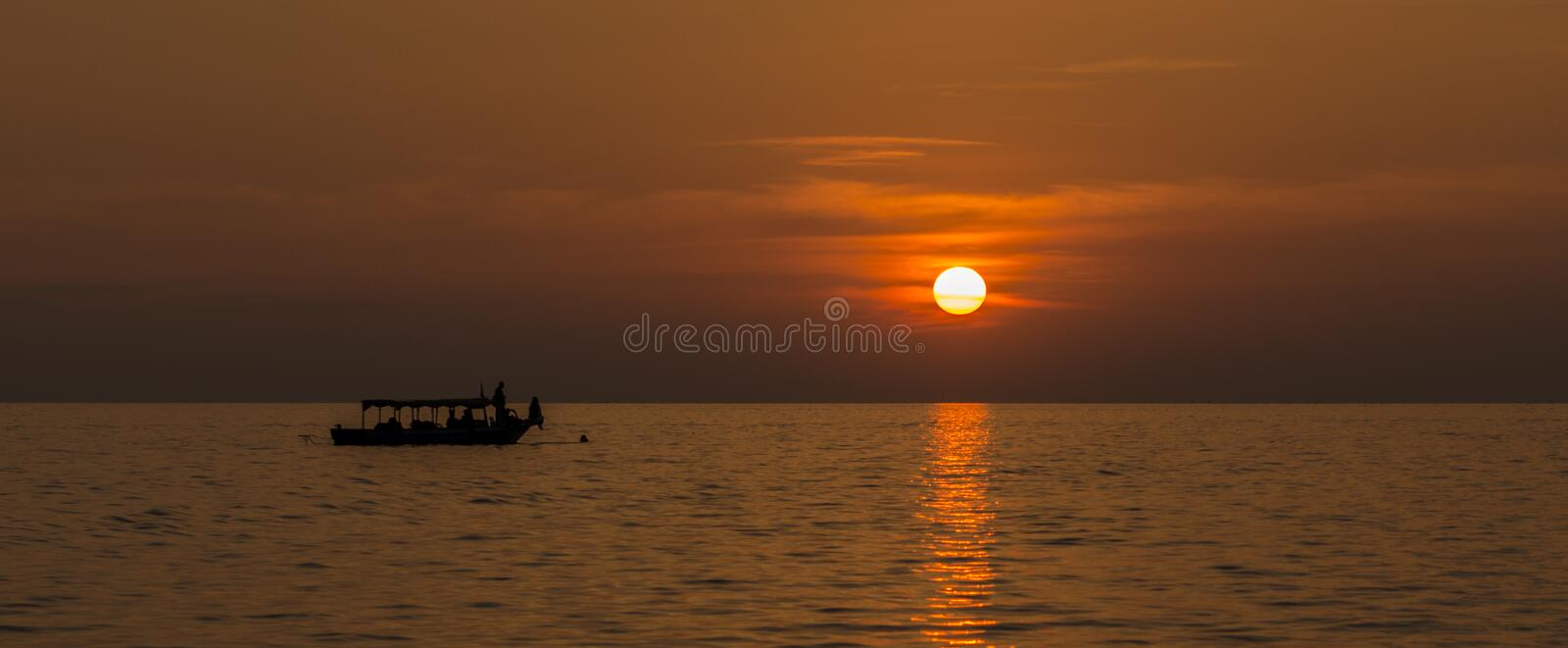 Sunset on the lake with a boat on the horizon. In warm colors stock images
