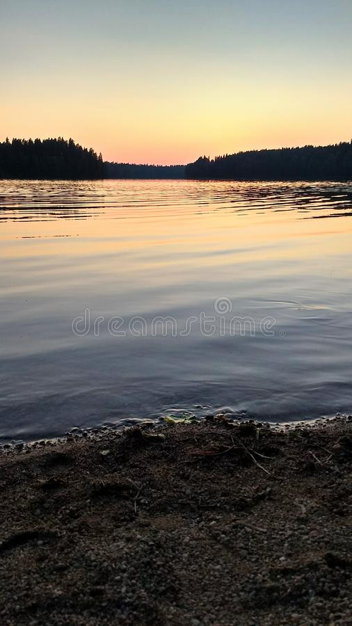 The sunset at the lake in colors of light blue, orange and pink stock photo