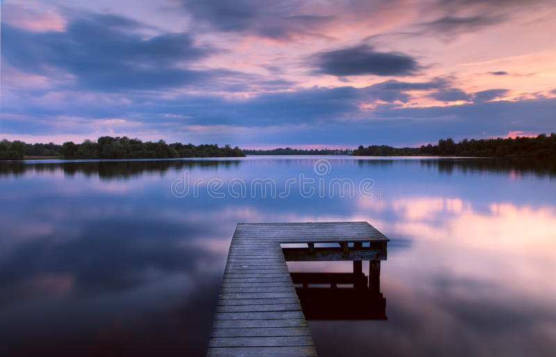 Sunset on lake from the pier royalty free stock photography