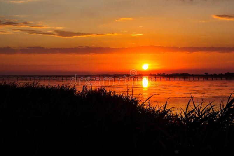 Sunset lake river landscape. Golden natural sky water sunset view of jetty or small bridge at horizon and orange sky above it with stock photo