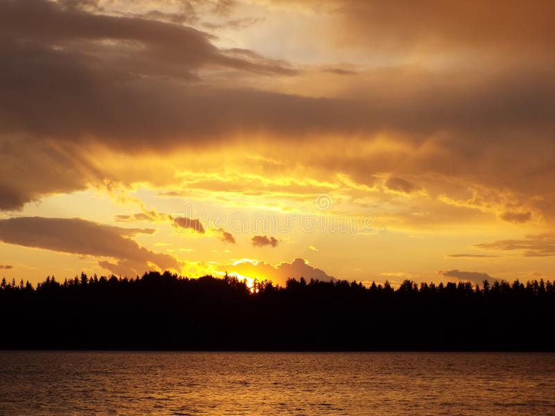 Sunset on the lake on a summer evening. The clouds are illuminated by the rays of the sun in yellow and orange light, visible ripples on the water royalty free stock photo