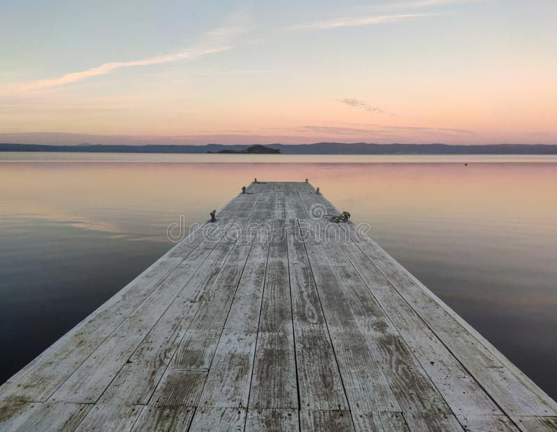 Winter Sunset on a lake with wooden Pier. Sunset on a lake with wooden Pier. With orange and red colors royalty free stock photography