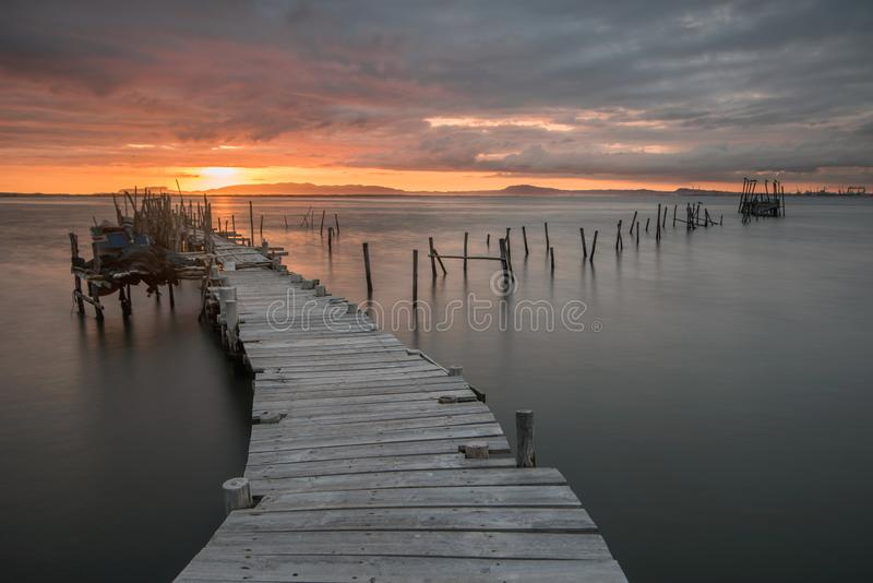Sunset landscape of artisanal fishing boats in the old wooden pier. Carrasqueira is a tourist destination for visitors to the coas. T of Alentejo near Lisbon stock photo