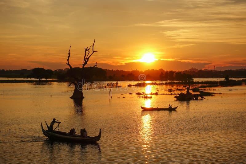 Famous U Bein bridge near Mandalay in Myanmar. Sunset landscape with boats near famous U Bein bridge near Mandalay in Myanmar stock image