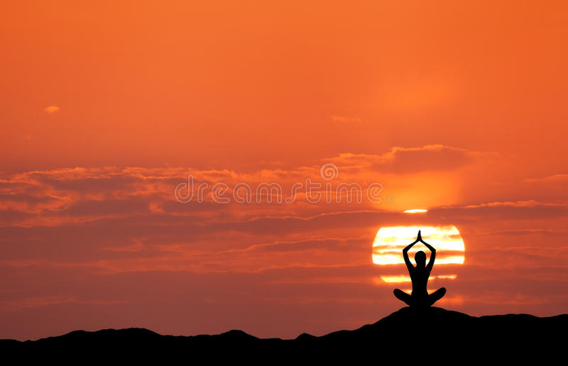 Sunset landscape with girl practicing yoga on the hill stock photos