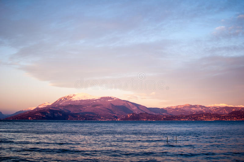 Sunset landscape of a lake with violet natural sunlight. Lago di Garda, Sirmione, Italy stock photos