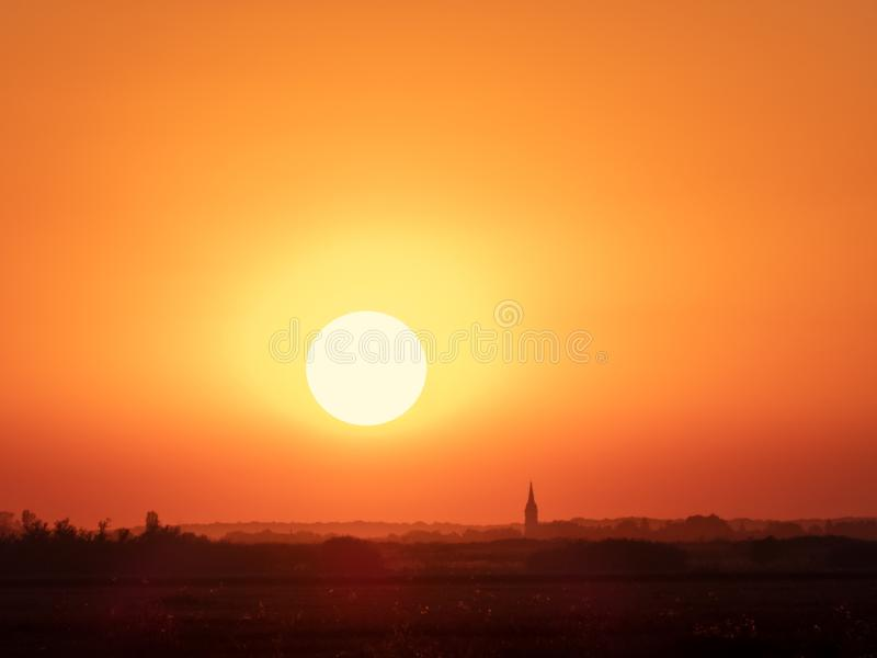 Sunset landscape with a plain wild grass field, big round bright sun on a orange clear sky and an old abandoned church. Pefect stock images