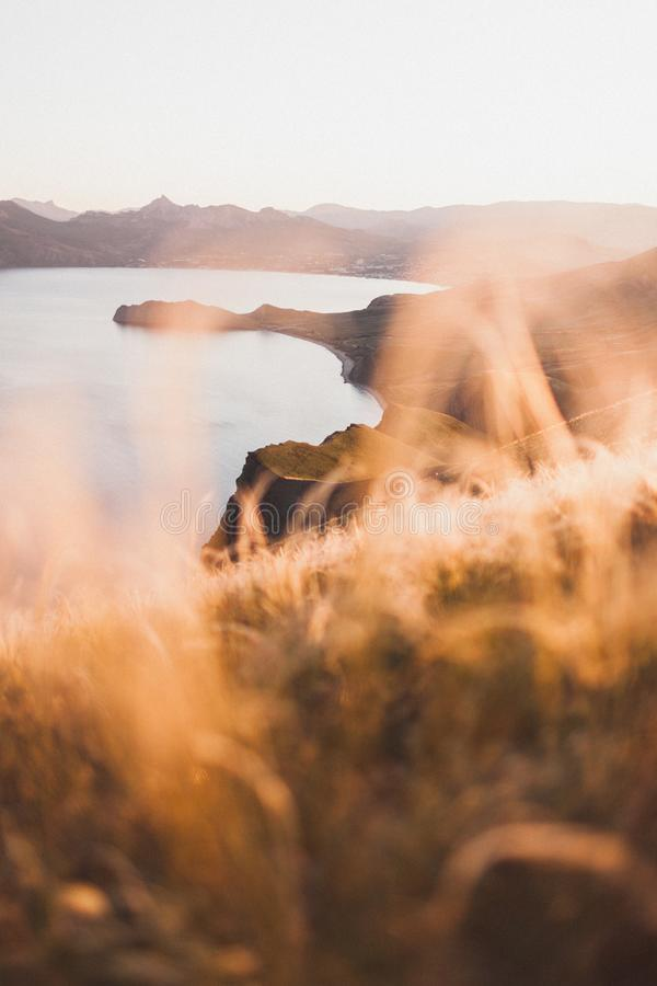 Sunset landscape of sea coast and spring field hill with feather grass. Sunset landscape overlooking the hilly coastal line in Crimea, Koktebel..Incredible royalty free stock images