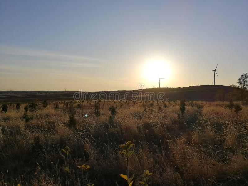 Sunset in late autumn and clean energy. In late autumn, sunsets are taken near a small mountain village in Fuxin City, Liaoning Province, China. Sunsets and royalty free stock photos