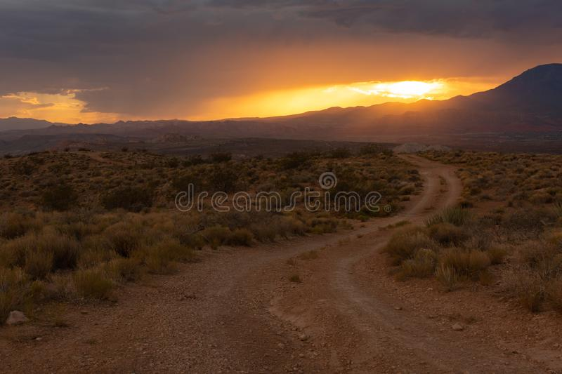 Sunset light glows orange over a landscape with a dirt road leading into the desert with the sun going down behind clouds royalty free stock photography