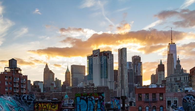 Sunset light shines behind the buildings of the lower Manhattan skyline in New York City royalty free stock photos