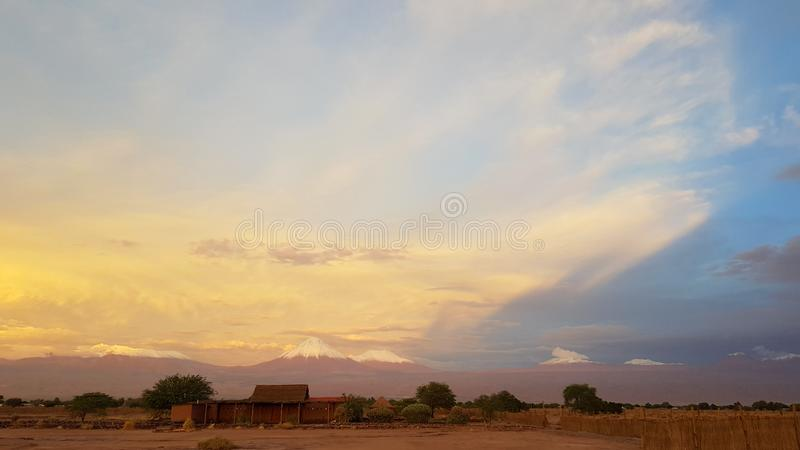 Sunset lights in the arid and desolate landscape of the Atacama Desert. And the peaks of the snowy volcanoes of the Andes cordillera in the background stock photo