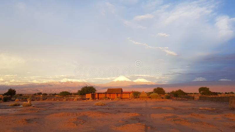 Sunset lights in the arid and desolate landscape of the Atacama Desert. And the peaks of the snowy volcanoes of the Andes cordillera in the background stock image