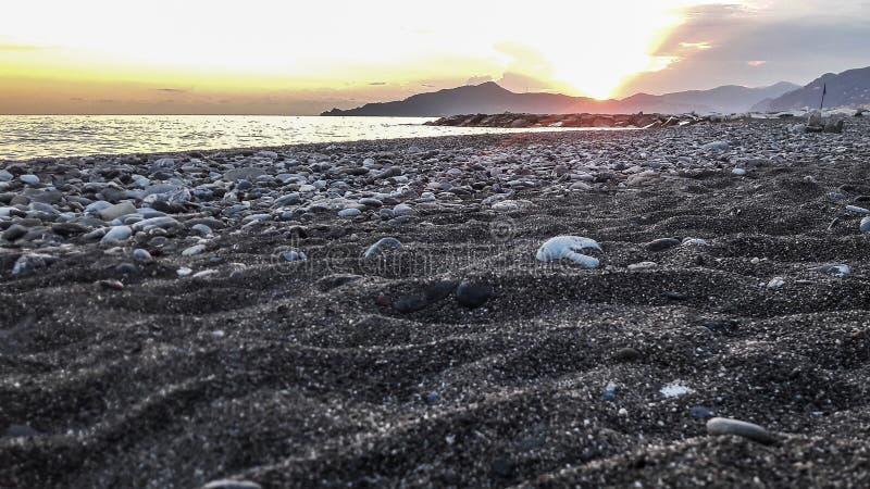Sunset on ligurian beach stock photography