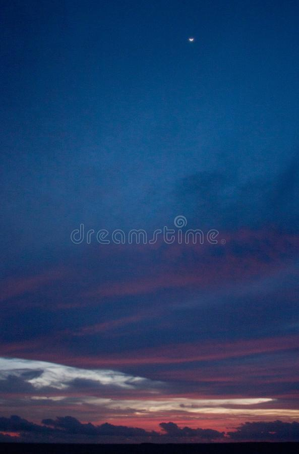 Sunset with a little Moon in the sky in Tonga royalty free stock photos
