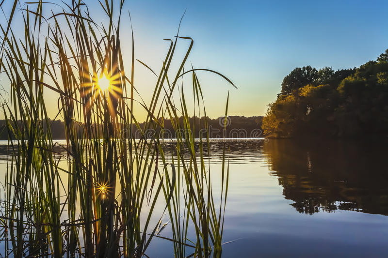 Sunset at Little Seneca Lake. The setting sun creates sunbursts and reflections on the calm water of Little Seneca Lake, Boyds, MD royalty free stock images