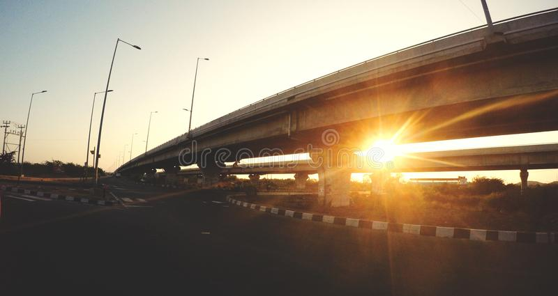 A lonely highway captured during sunset. The sunset , the lonely highway and bridges ..beautiful golden hour capture taken using GoPro .. place : chennai, india stock images