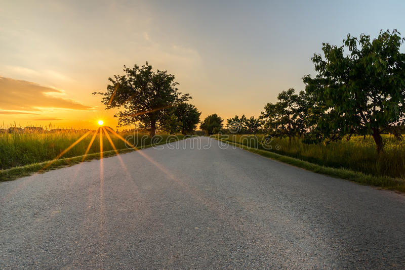 Sunset with long orange beams over the lone road royalty free stock image