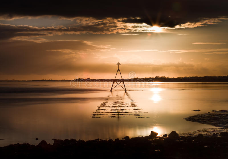Sunset at The Loughor Estuary. Sunset and Cardinal Marker at The Loughor Estuary, Llanelli, South Wales stock photo