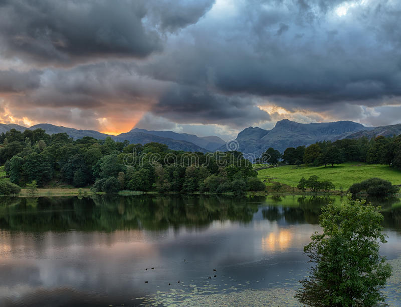 Sunset at Loughrigg Tarn in Lake District. Sun setting over Langdale Pikes with Loughrigg Tarn in foreground royalty free stock images