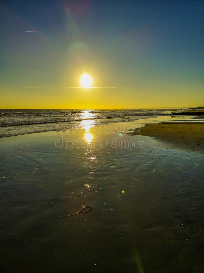 Sunset and Low Tide in Bexhill, East Sussex, England 1. The glistening sand and evening sun make for a beautiful poster or print for home or office decor usage stock images