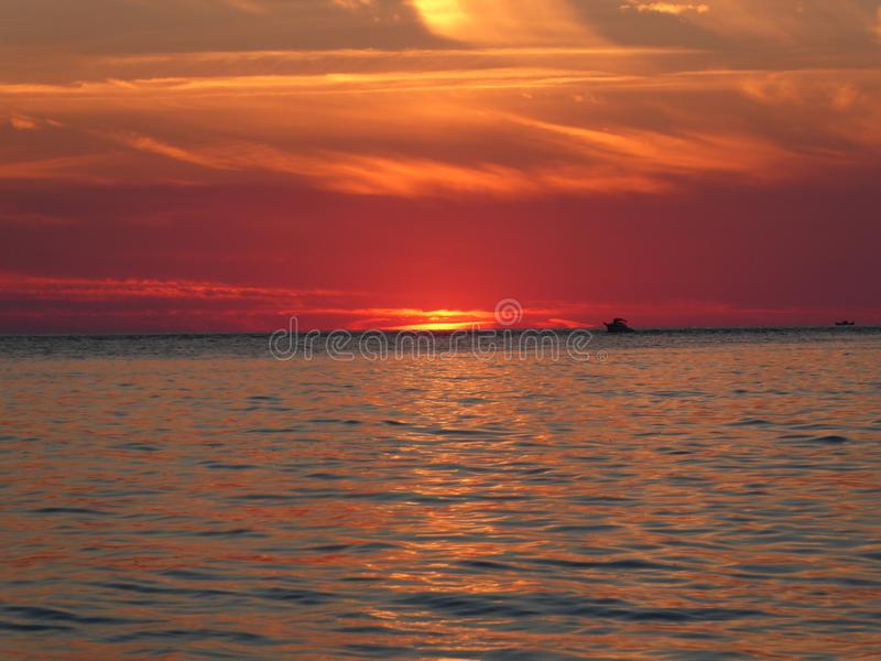 Sky on Fire - shortly before the sun is gone for the day. Sunset magical red glowing waves water ocean sea evening dawn sky fire shortly gone day stock image