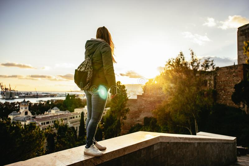 Sunset in Malaga, Spain. Young woman with backpack stands on a wall watching the horizon. Mediterrenean town and sea. royalty free stock photography