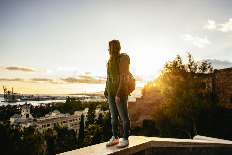 Sunset in Malaga, Spain. Young woman with backpack stands on a wall watching the horizon. Mediterrenean town and sea. stock photo