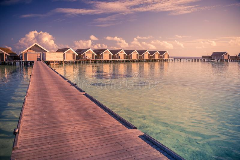 Sunset on Maldives island, long wooden jetty and luxury water villas royalty free stock photography