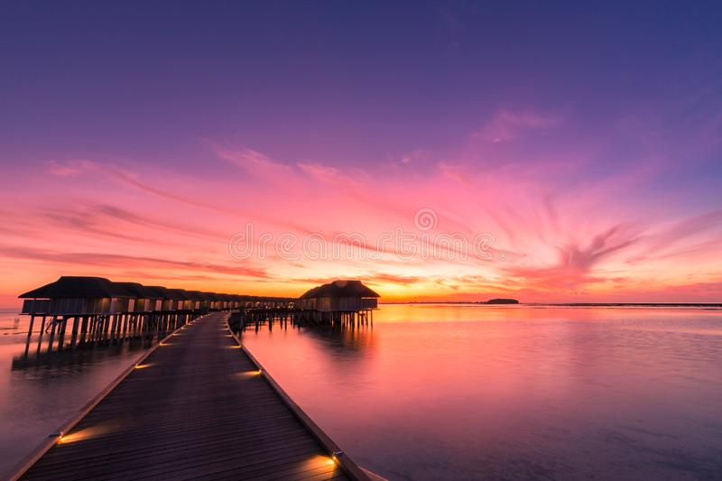 Sunset on Maldives island, luxury water villas resort and wooden pier. Beautiful sky and clouds and beach background stock images