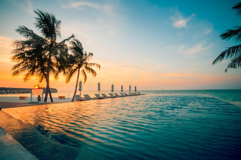 Sunset on Maldives island, luxury water villas resort and wooden pier. Beautiful sky and clouds and beach background for summer. Beautiful Maldives island beach stock photo