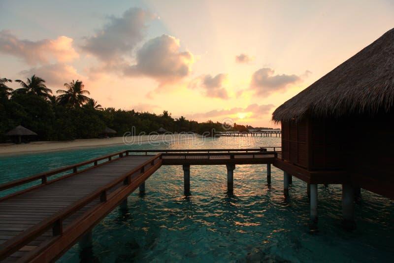 Sunset on Maldives island, water villas resort stock images