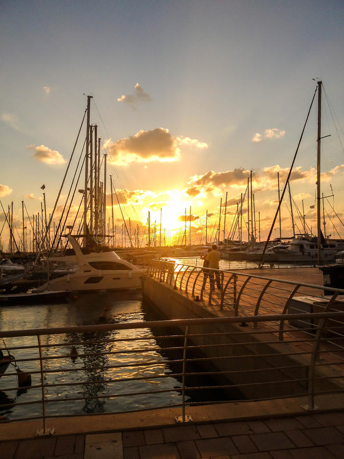 Sunset in a marina. On the average plan the young couple admires a view of a close formation of yachts on orange sunset background royalty free stock images
