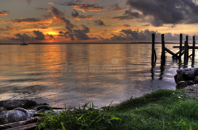 Sunset with piers Fernandina Beach Amelia Island Florida. Sunset, clouds and harbor from the marina overlooking the St. Marys River at Fernandina Beach, Amelia stock images