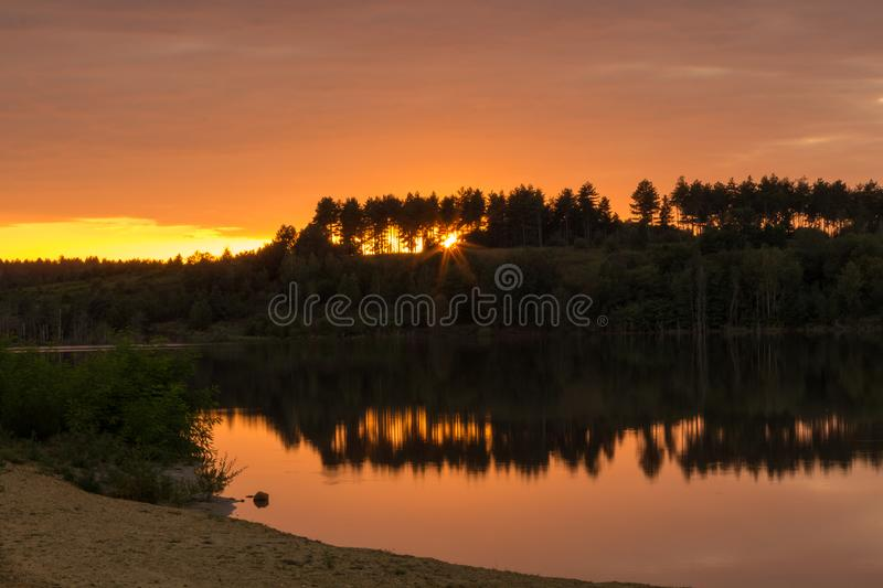 Sunset at the Mechelse Heide ith a scenic view of being on the beach with sand and water and hard shadows of rocks royalty free stock photo
