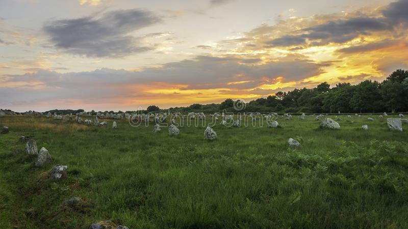 Sunset in the megalithic alignment of Carnac. The rocks rest in a green meadow for thousands of years, summer begins to dry the grass and the sun hides behind royalty free stock photography