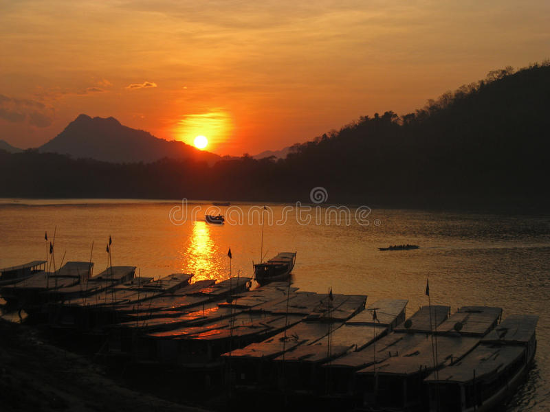 Sunset on the Mekong River in Laos. With traditional boats royalty free stock photography