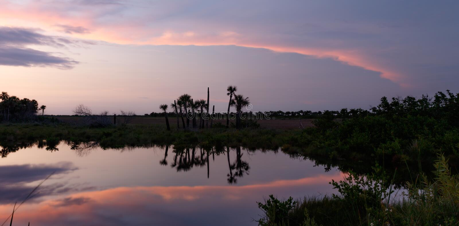 Sunset at Merritt Island National Wildlife Refuge, Florida. Sunset with clouds reflecting in a pond at Merritt Island National Wildlife Refuge, Florida, USA royalty free stock images
