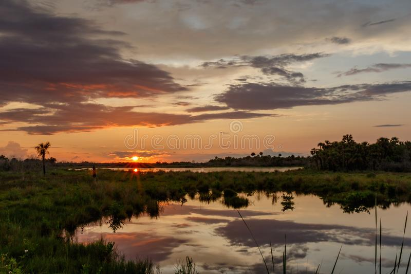 Sunset at Merritt Island National Wildlife Refuge, Florida. Sunset with clouds reflecting in a pond at Merritt Island National Wildlife Refuge, Florida, USA stock images