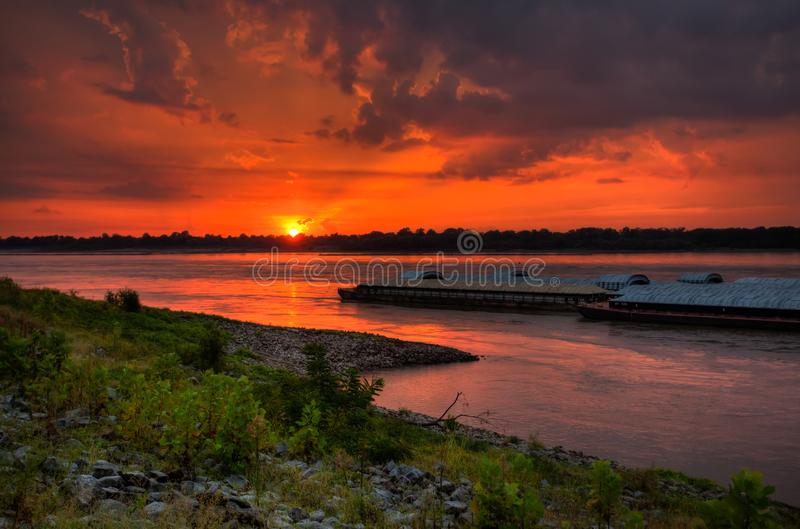 Sunset on the Mississippi River Barges Traveling the waterway. Industrial barges on the Mississippi River ferrying goods and products cross country on the river royalty free stock image