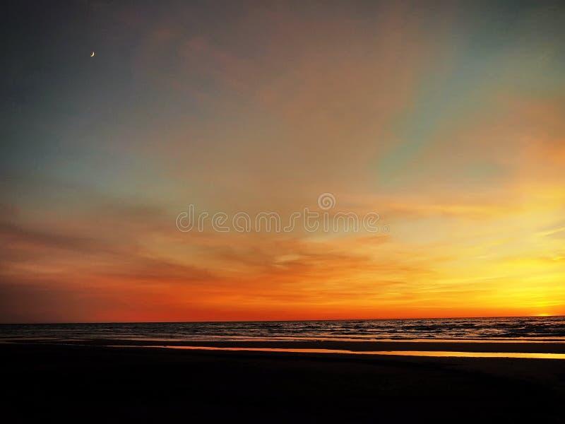 Sunset and moon on blue orange sky royalty free stock photos
