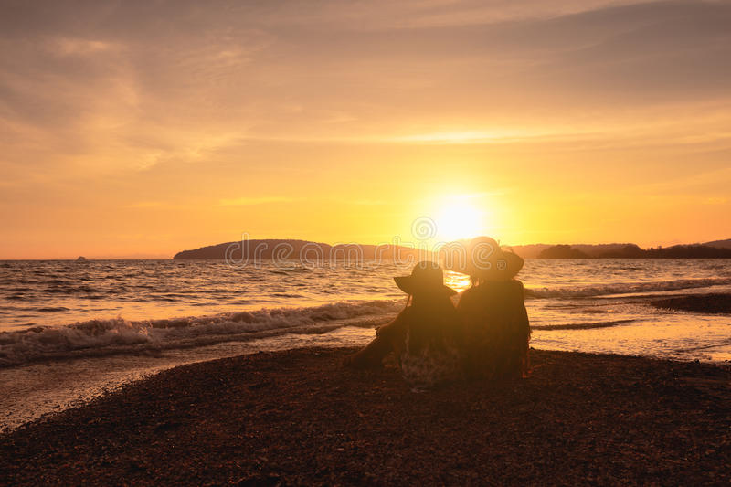 Sunset. Mother and daughter sitting at the beach looking sunset stock image